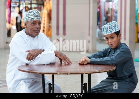 Omani uomo e suo figlio seduto fuori la Mutrah souk in Muscat, la capitale del sultanato di Oman. Foto Stock