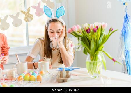Ragazza adolescente a tavola la lettura di testi sullo smartphone mentre la tintura di uova sode per la Pasqua Foto Stock