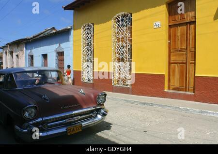 Case colorate in una scena di strada. Vecchio rosso Chevrolet Classic American automobile parcheggiata su una strada Foto Stock