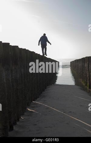 Silhouette di un uomo maturo in equilibrio su palo di legno sulla spiaggia, Renesse, Schouwen-Duiveland, Zeeland, Foto Stock
