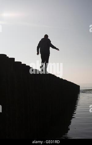 Silhouette di un uomo maturo in equilibrio su palo di legno in spiaggia, Renesse, Schouwen-Duiveland, Zeeland, Paesi Foto Stock