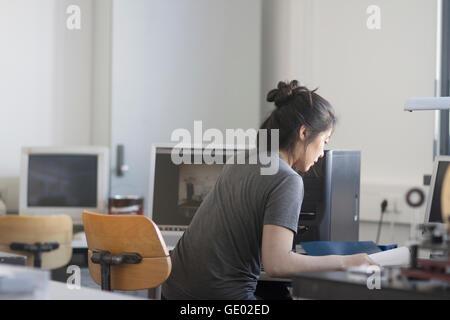 Femmina giovane ingegnere di lavoro sul computer in un ufficio di Freiburg im Breisgau, Baden-Württemberg, Germania Foto Stock