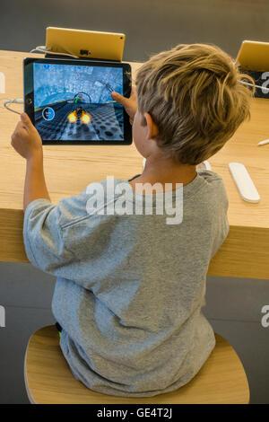 Un giovane ragazzo 7-8 anni gioca un gioco su un iPad all'Apple Store di Santa Barbara in California. Foto Stock