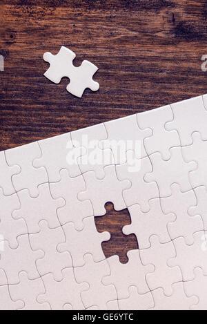 Puzzle con un pezzo mancante a sinistra per completare, copia spazio, vista dall'alto Foto Stock