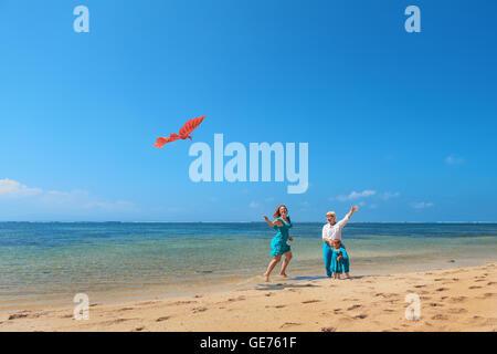 La famiglia felice sulla spiaggia - nonna, madre, Baby girl divertirsi, donna corre lungo mare surf con spruzzi Foto Stock