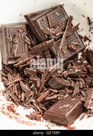 Barra di cioccolato e trucioli di una vaschetta di colore bianco Foto Stock