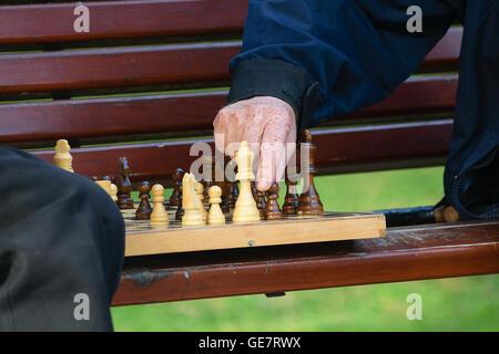 Amici di vecchia data e tempo libero. Due anziani divertirsi e giocare a scacchi gioco al parco sulla panchina. Foto Stock