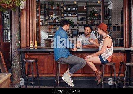 Un gruppo di giovani amici seduti e parlare in un bar. Giovani uomini e donne riuniti in una caffetteria. Foto Stock