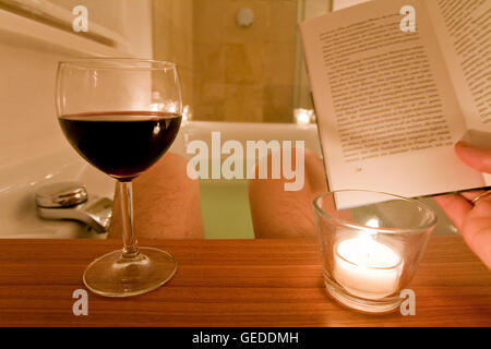 Uomo seduto in una vasca da bagno, balneazione, la lettura di un libro, bere vino, candele, spa, rilassante Foto Stock