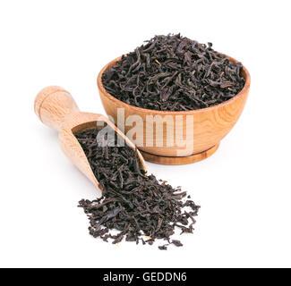 Tè nero foglie secche in una ciotola di legno isolato su bianco Foto Stock
