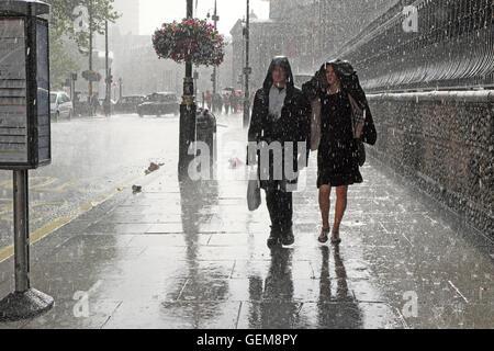 Persone che camminano in pesante pioggia battente in bagnato estate 2016 su una strada di città in Charing Cross, Foto Stock