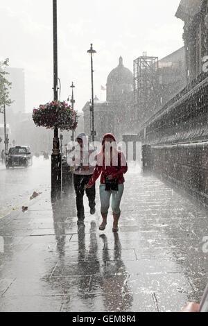 Persone che camminano in heavy rain in bagnato estate 2016 in una strada a Charing Cross, Londra UK KATHY DEWITT Foto Stock