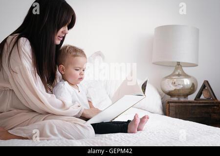 Un fortemente incinta Donna che gioca con il suo giovane figlio. Seduta su un letto, la lettura di una storia. Foto Stock