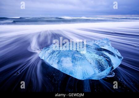 Lavaggio onde attorno ad un piccolo iceberg sulla spiaggia a Jokulsarlon in Islanda. Foto Stock