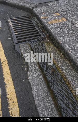 Il drenaggio di strada / grondaia in Truro, Cornwall. Metafora visiva per 'strumenti giù il drain' e acqua rifiuti Foto Stock