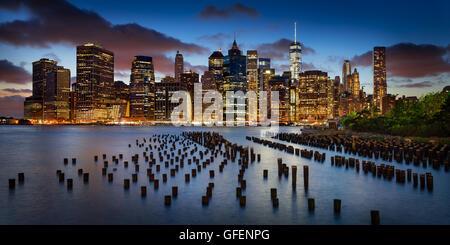 Panoramica di Lower Manhattan Financial District al crepuscolo con molo vecchio palificazioni di legno e il World Trade Center. La città di New York