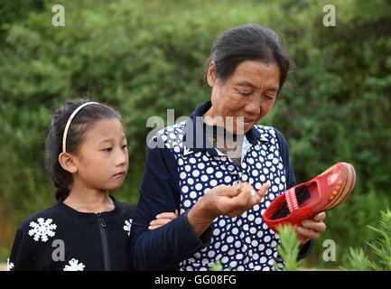 (160803) -- XUNDIAN, 3 Agosto, 2016 (Xinhua) -- la nonna mende una calzatura per un 10-anno-vecchio egli Yuanxi Foto Stock