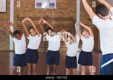 Insegnante di esercizio di insegnamento ai ragazzi delle scuole nel campo di pallacanestro Foto Stock