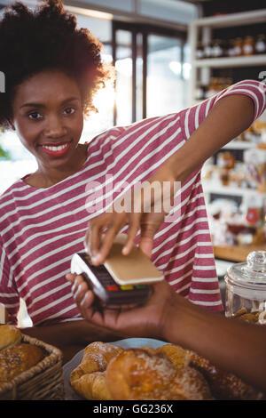 Donna sorridente il pagamento fattura tramite lo smartphone utilizzando la tecnologia NFC Foto Stock