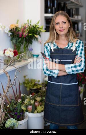 Ritratto di una donna felice in piedi nel suo negozio di fiori Foto Stock