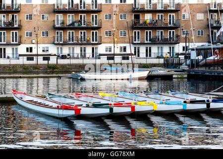 Fila di barche decorate con colori differenti, ormeggiata in Millwall Dock esterno a Londra Foto Stock