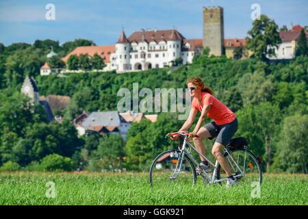 Donna in bicicletta, castello di Neubeuern in background, Neubeuern, Alta Baviera, Baviera, Germania