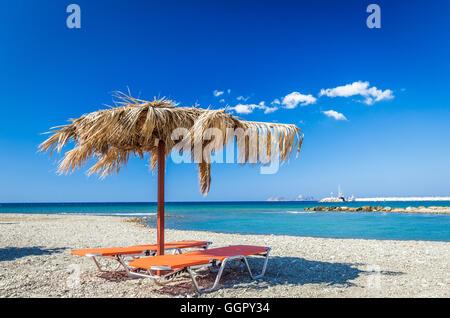 Ombrello di paglia su una spiaggia di sabbia in Grecia. Sedie da spiaggia con ombrelloni su una bellissima spiaggia Foto Stock