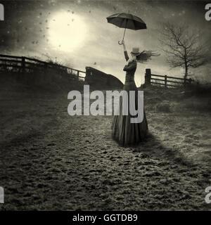 Giovane donna come sposare Poppins con ombrellone in piedi nei campi Foto Stock