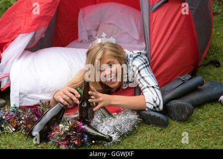 Donna appoggiata fuori da una tenda con vuoti di bottiglie di alcol Foto Stock