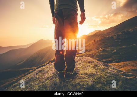 Giovane uomo Traveler piedi in piedi da sole al tramonto con le montagne sullo sfondo stile di vita concetto di Foto Stock