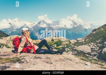 Donna felice Traveler seduta rilassante montagne paesaggio sereno su sfondo stile di vita viaggio concetto Avventura Foto Stock