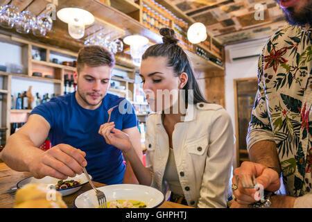 Giovani cenare presso il contatore nel ristorante Foto Stock