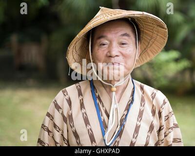Anziani Okinawense l uomo nella sua 70's indossando il tradizionale stile bashofu kimono e cappello di paglia. Okinawa Foto Stock