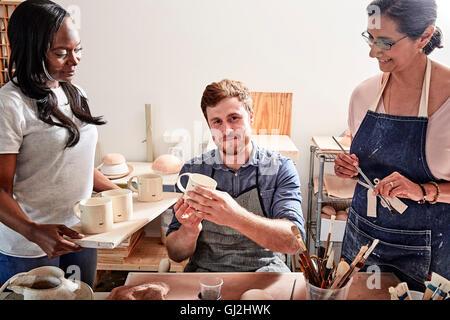 Gruppo di persone pittura ceramica in officina Foto Stock