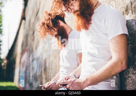 Giovane maschio hipster gemelli con la barba rossa appoggiata contro la parete texting sugli smartphone Foto Stock