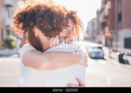 Giovane maschio hipster gemelli con i capelli rossi e le barbe costeggiata sulla strada di città Foto Stock