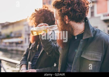 Giovane maschio hipster gemelli con i capelli rossi e le barbe di bere birra sul canal waterfront Foto Stock