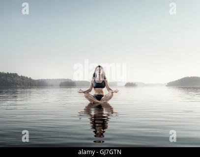 Giovane donna pratica ancora sedute di meditazione. Donna meditando su una piattaforma in acqua sul lago di prima Foto Stock