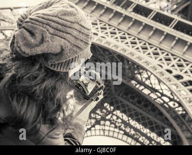Giovane ragazza in viaggio e preso le immagini della Torre Eiffel, con fotocamera. Foto Stock