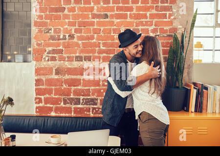 Ritratto di giovane uomo saluto una donna al cafe. Giovane uomo abbracciando la sua fidanzata a un coffee shop. Foto Stock