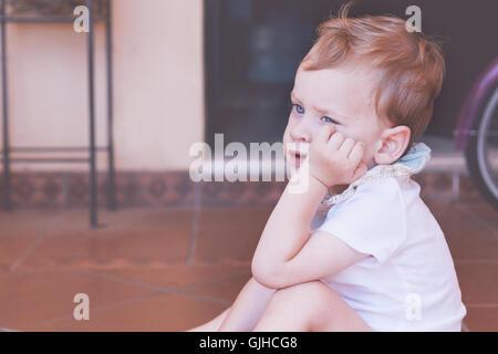 Ragazzo seduto sul pavimento con la mano sul mento Foto Stock