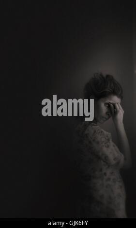 Triste,giovane donna in piedi in camera dalla finestra che copre il volto Foto Stock
