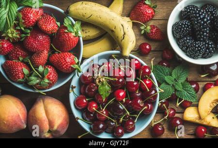Estate frutta fresca e bacche di varietà su uno sfondo di legno, vista dall'alto, composizione orizzontale Foto Stock