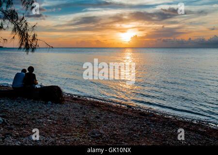 Un paio in silhoutte seduto su un log sotto un albero a godersi il tramonto tropicale sulla spiaggia. Foto Stock