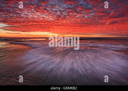 Sfocata onda veloce al golden ora oltre il piano fondale roccioso intorno al rock pool di Mona Vale Beach a Sydney.