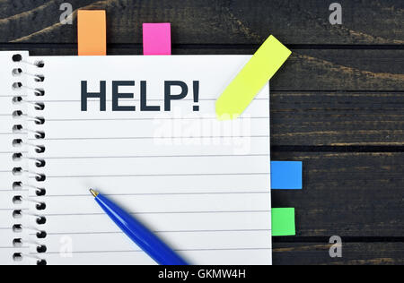 Aiuto parola sul blocco note e penna Foto Stock