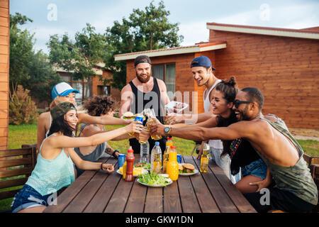 Un gruppo di giovani felici hanno celebrando e aver parte all'aperto Foto Stock