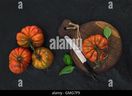 Fresche e mature hairloom i pomodori e le foglie di basilico rustico di legno Foto Stock