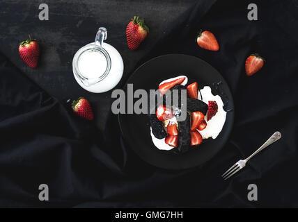 Nero biscotti e dessert di fragole con panna dolce su sfondo nero Foto Stock