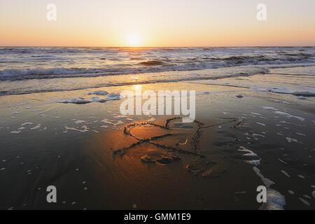 La figura cuore trafitto da una freccia disegnata sulla spiaggia sabbiosa lambita dalle onde. Foto Stock